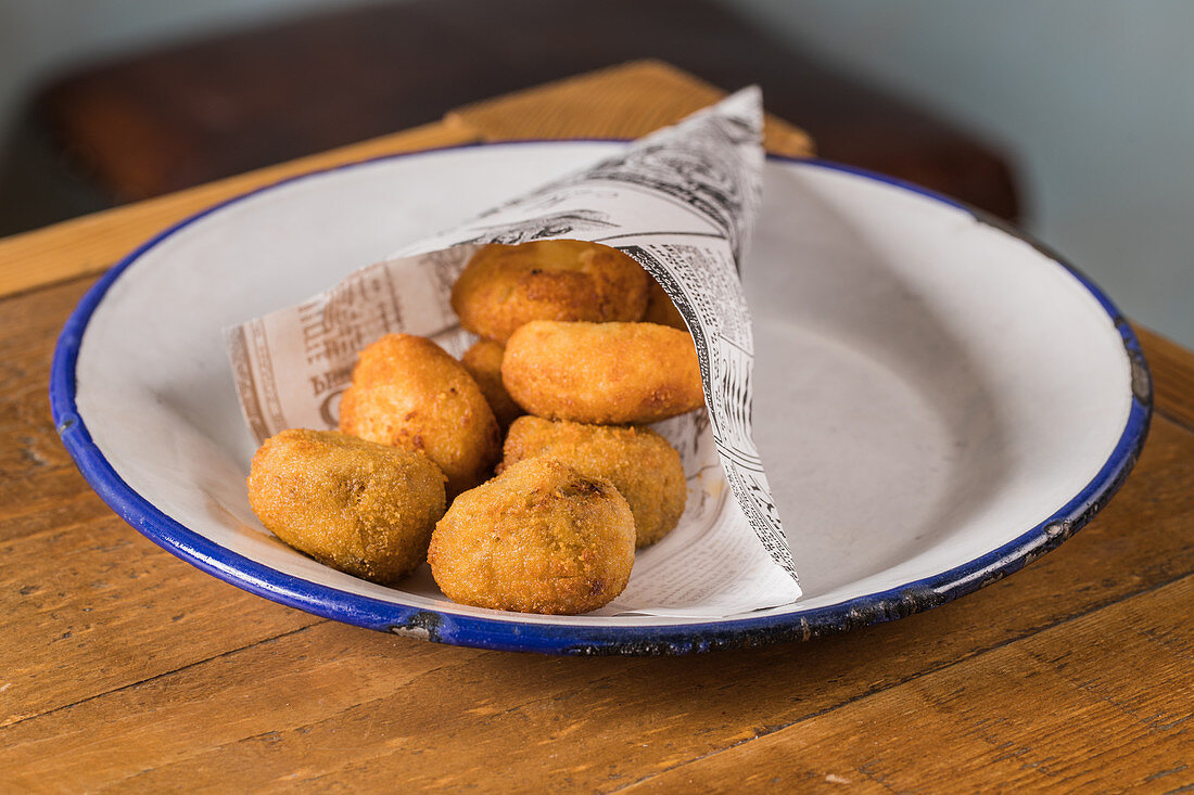 Potato croquettes on plate placed on wooden table in cafeteria