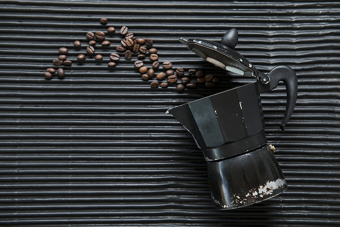 Traditional coffee maker placed on table with roasted coffee grains