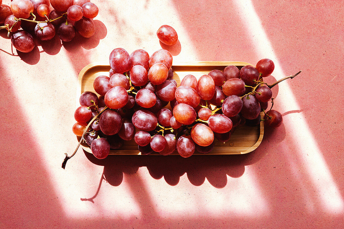 Bunch of delicious fresh juicy red grapes served on wooden tray on pink background
