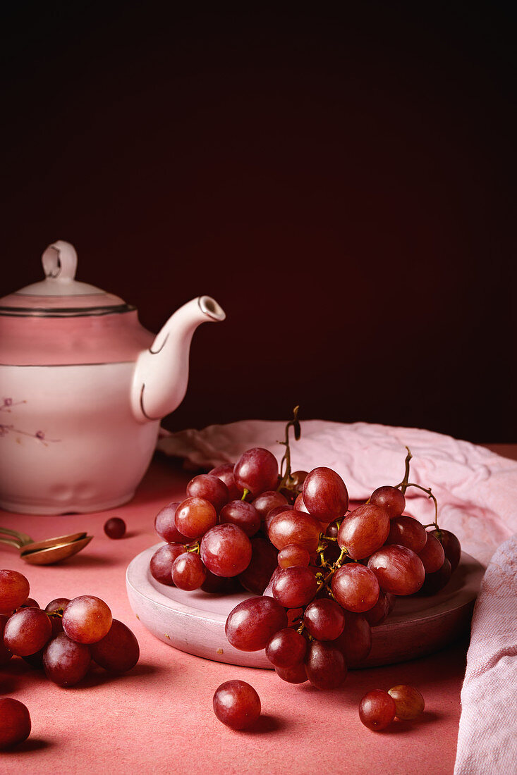 Still life composition with white porcelain teapot and tea spoon placed on round table