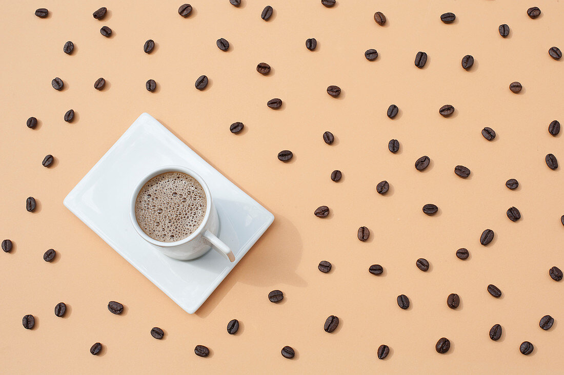 Mug with fresh hot coffee served on white tray on beige surface with scattered coffee beans