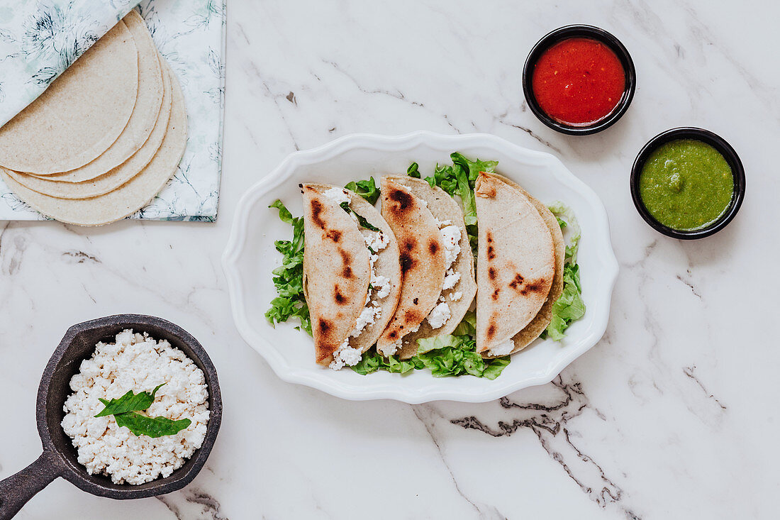 Tortillas with fresh quark cheese placed on plate with lettuce leaves, bowls of avocado and tomato sauces