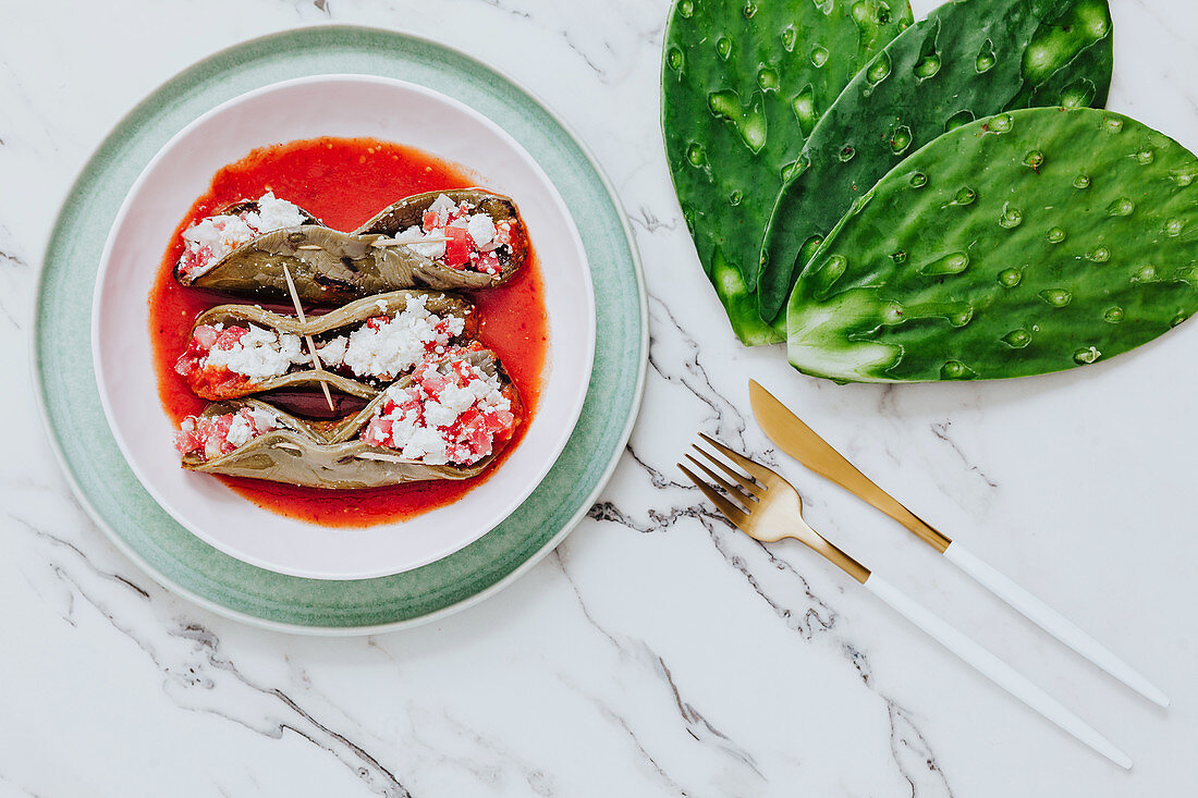 Roasted cactus leaves with tasty mix in tomato sauce, golden cutlery and fresh ingredient