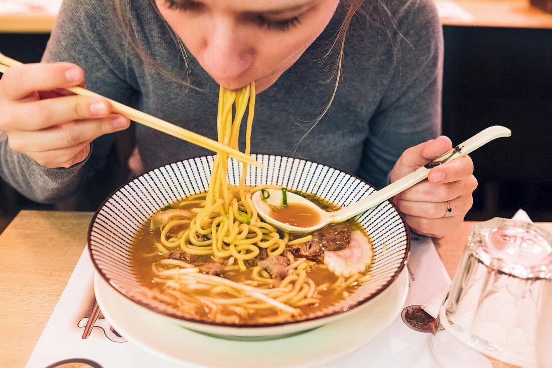 Junge Frau isst Ramen-Suppe mit Essstäbchen und Löffel in japanischem Restaurant
