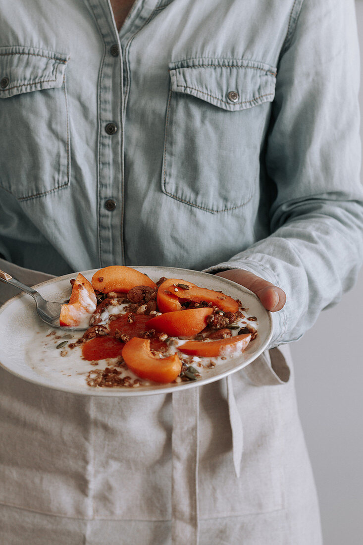 Unrecognizable person standing with bowl of healthy granola with yogurt and fresh fruits