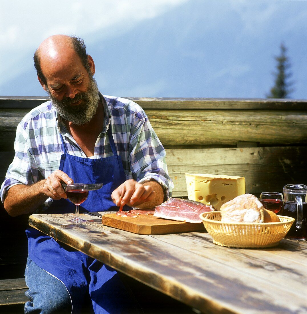 S. Tyrolean farmer enjoying afternoon snack of bacon & red wine