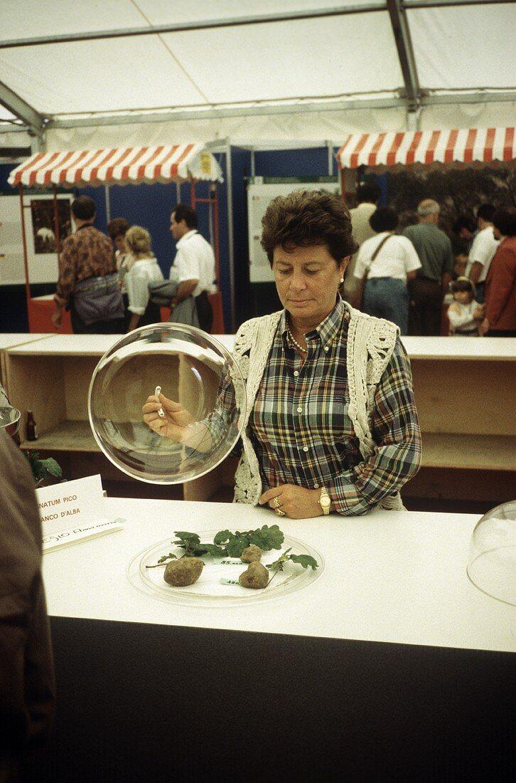 Truffle market in Alba: tradeswoman lifting up glass dome