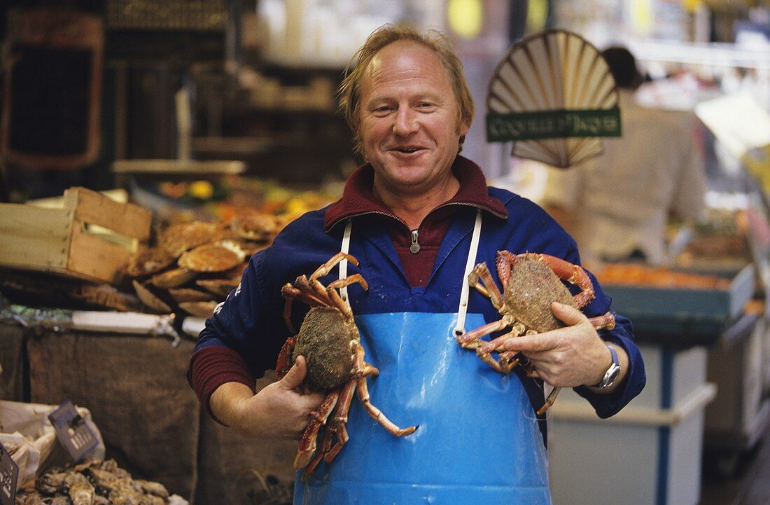 Trader with two crabs in his arms (market hall)
