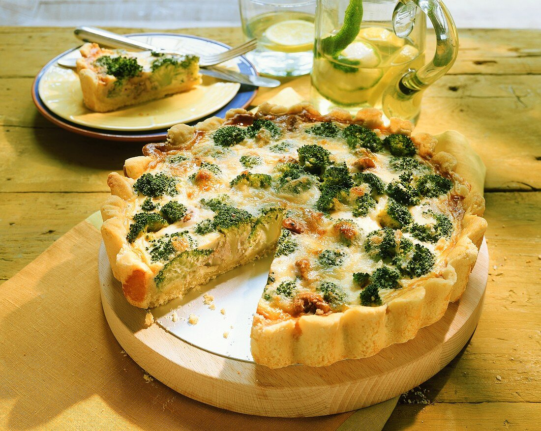 Broccoli quiche with cheese, pieces cut, one piece on plate