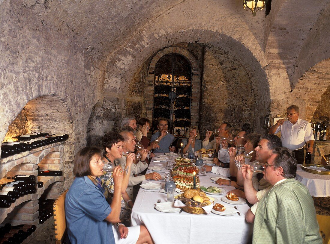 People in wine bar drinking wine at laid table
