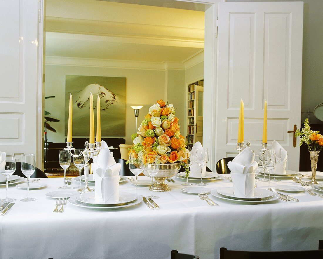 An elegant table with an arrangement of roses in a silver bowl and the views through the door into the living room