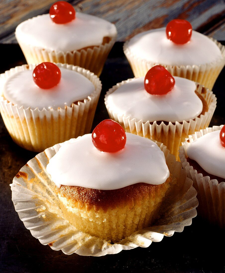 Iced muffins with cherries on top in paper cases