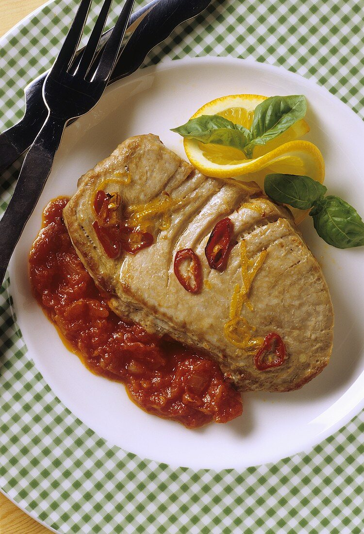 Tuna steak with tomato & orange sauce on plate