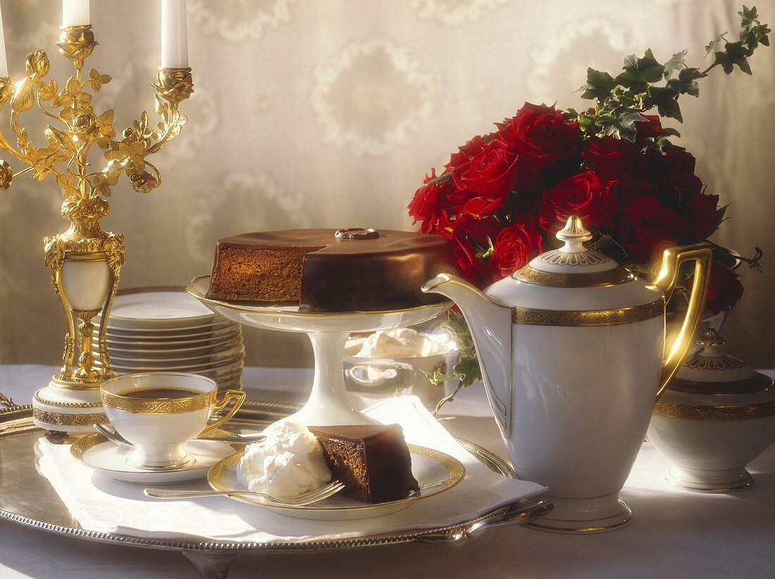 Sacher Torte on festive coffee table, décor: roses