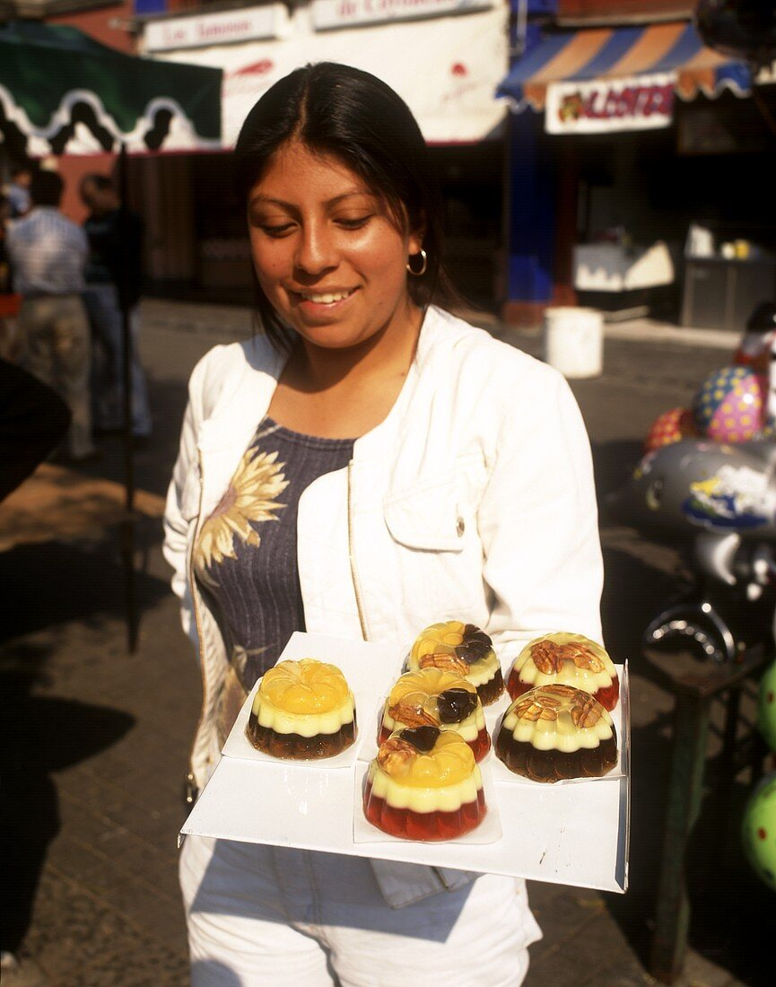 Mexican woman holding plate of sweet jelly tarts (in open air)