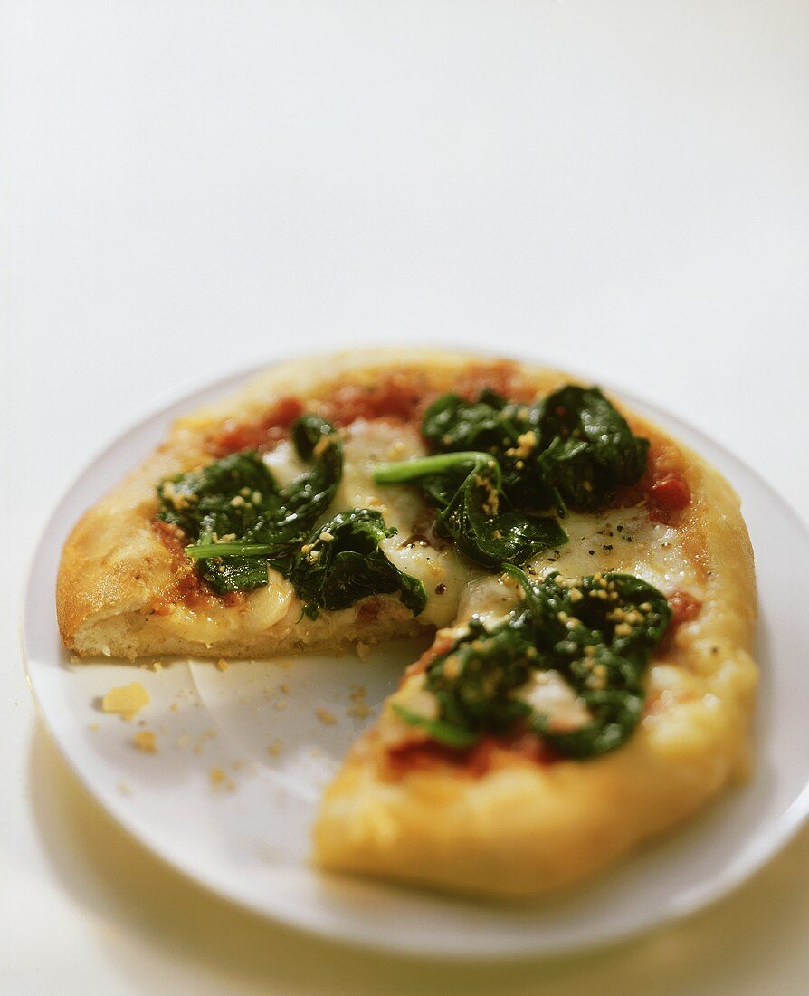 Pizza with tomatoes, cheese and spinach on plate