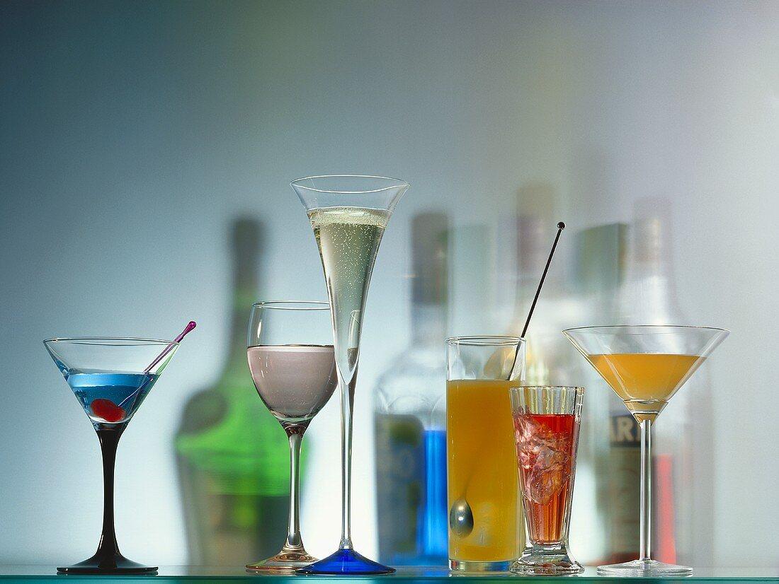 Bunte Cocktails in Gläsern & Farbschatten von Flaschen