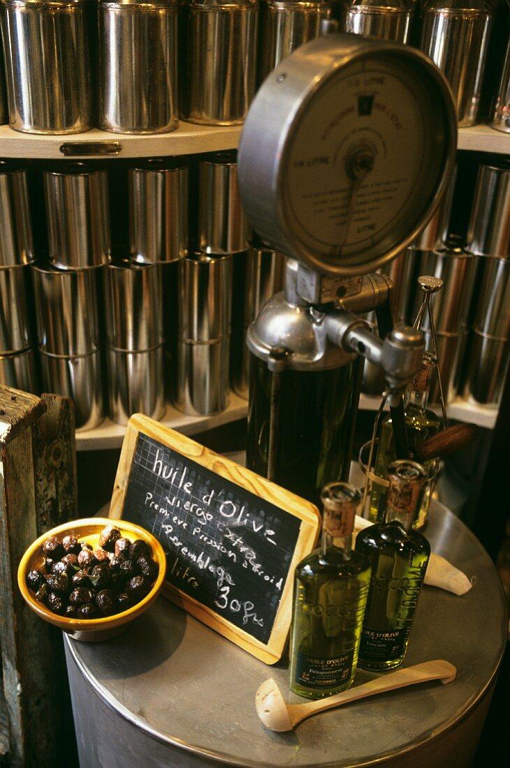Zwei Olivenölflaschen & schwarze Oliven auf Abfüllmaschine