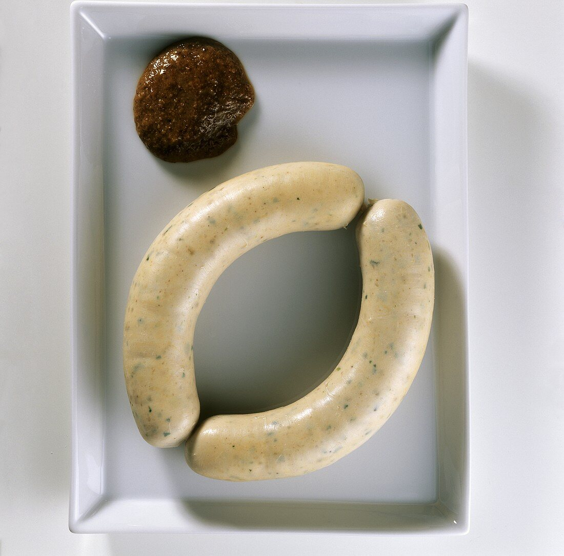 A pair of Weisswurst (Bavarian sausages) and sweet mustard