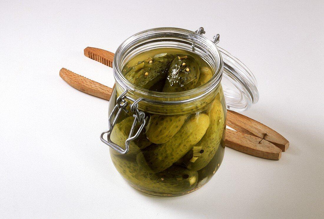 Gherkins in pickling jar, pickle tongs beside it