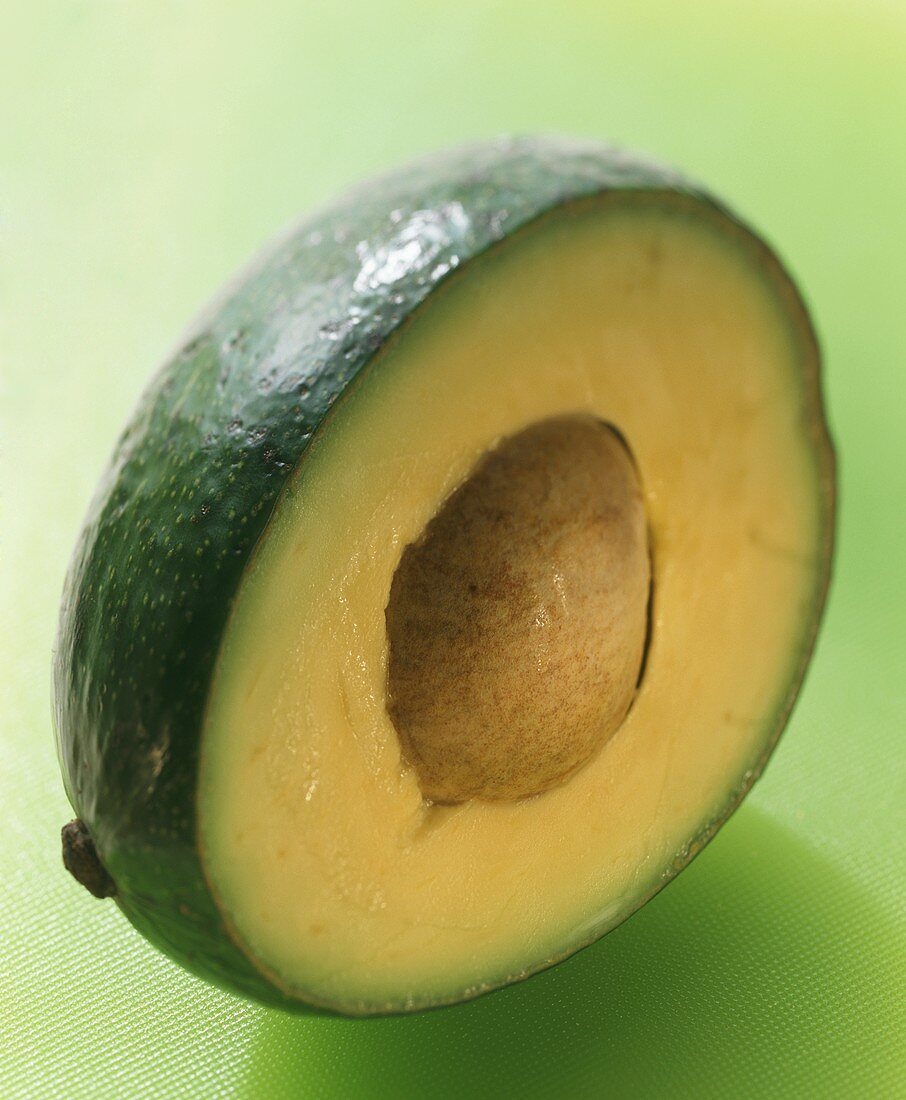 Half an avocado with stone on light-green background