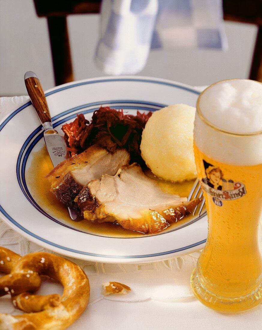 Roast pork with red cabbage & dumpling, beside it beer, pretzel