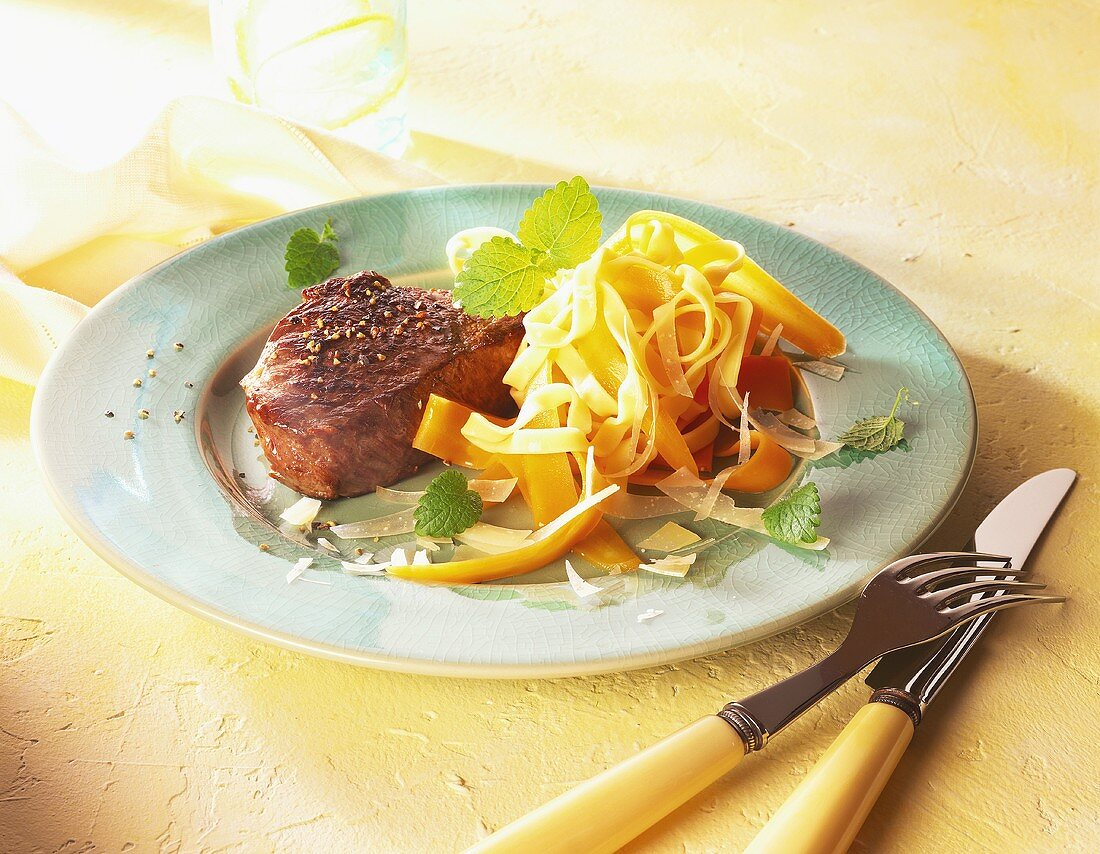 Peppered steak with vegetable pasta on plate