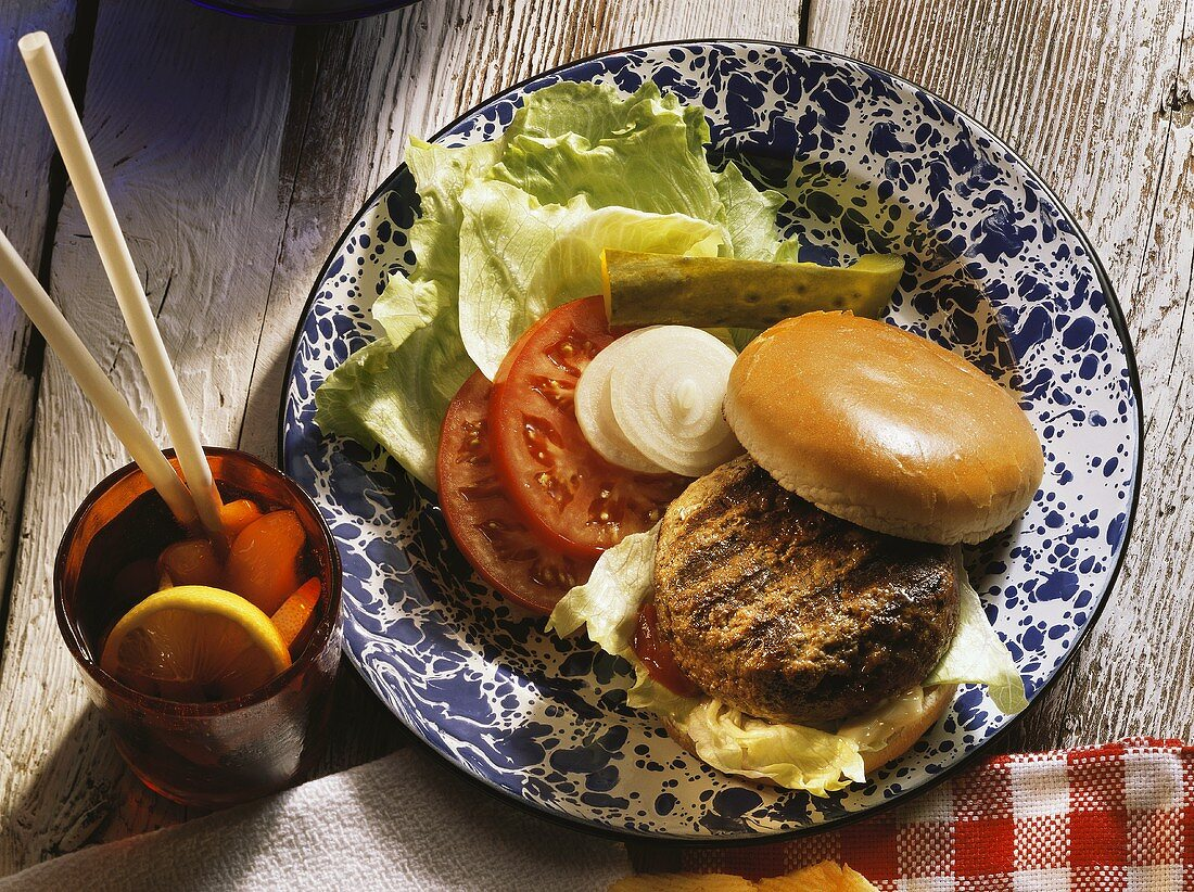 Hamburger on plate with salad and a drink