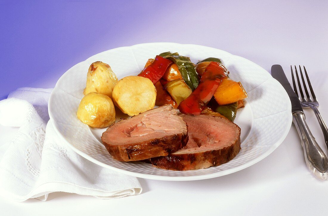Two slices of rolled roast pork with potatoes, peppers