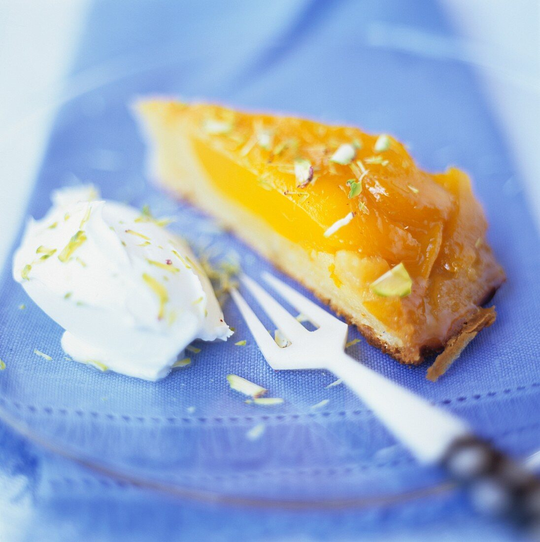 A piece of caramelised mango tart with cream on a plate