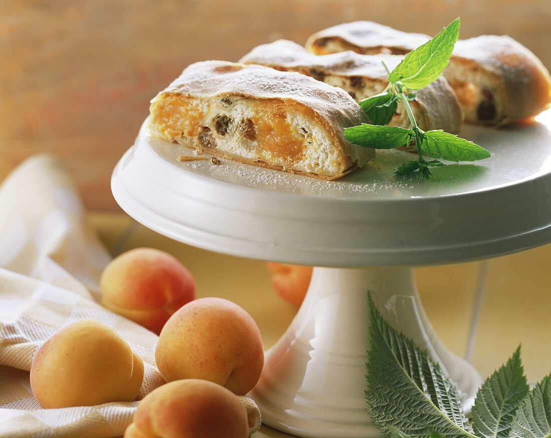 Curd cheese strudel with apricots on cake plate