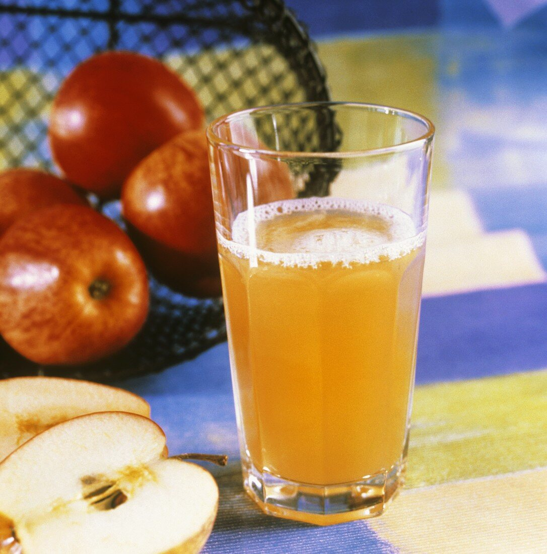 A glass of naturally cloudy apple drink & fresh apples