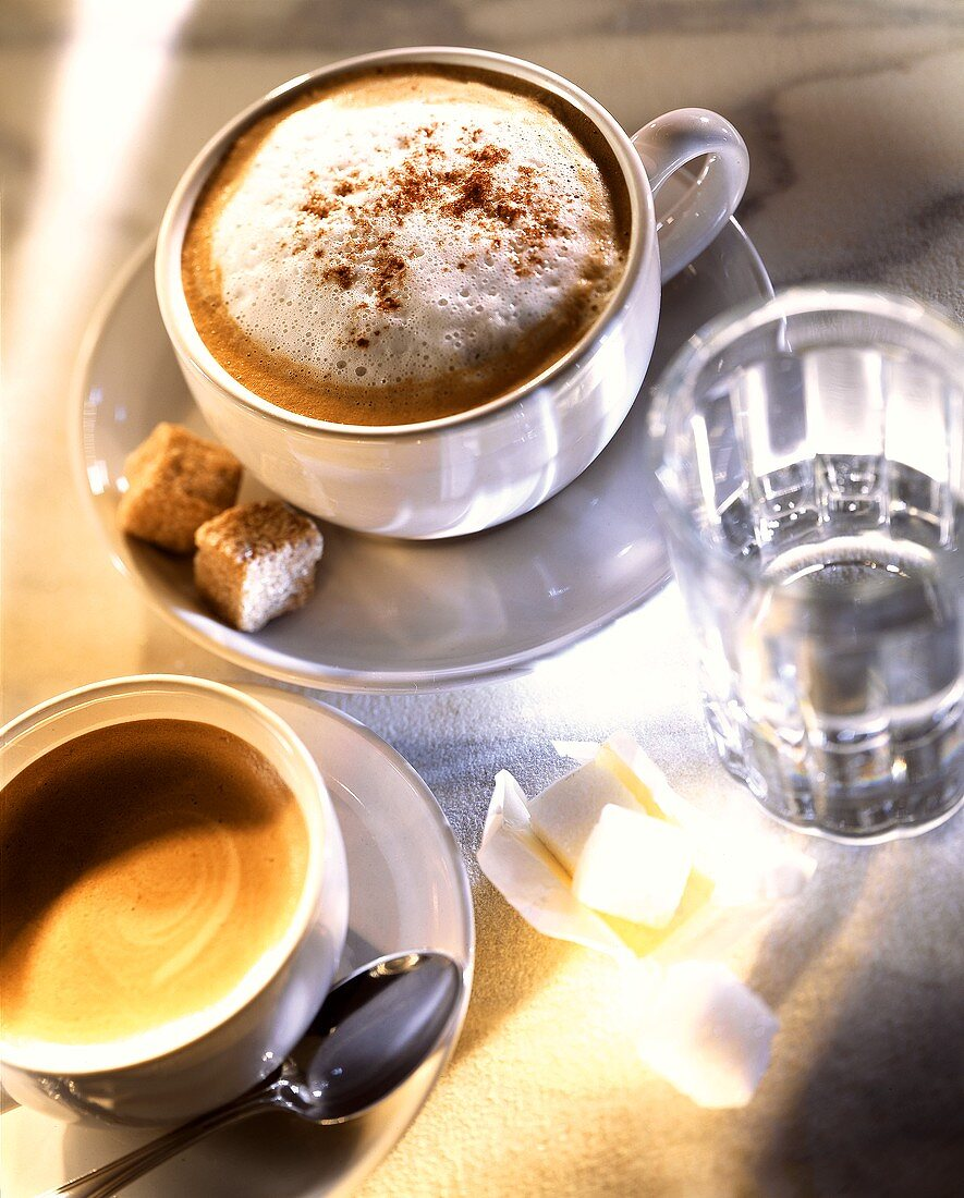 Cup of cappuccino, coffee, glass of water and sugar