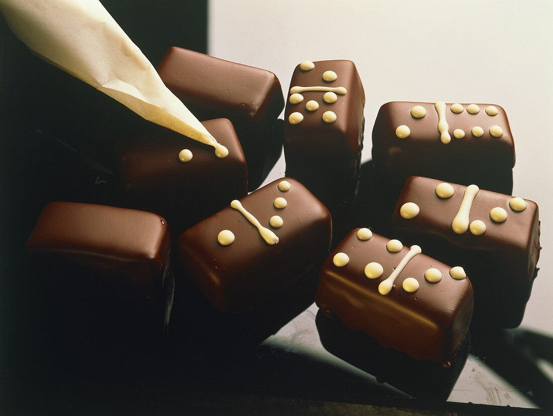 Dominoes being decorated with white chocolate