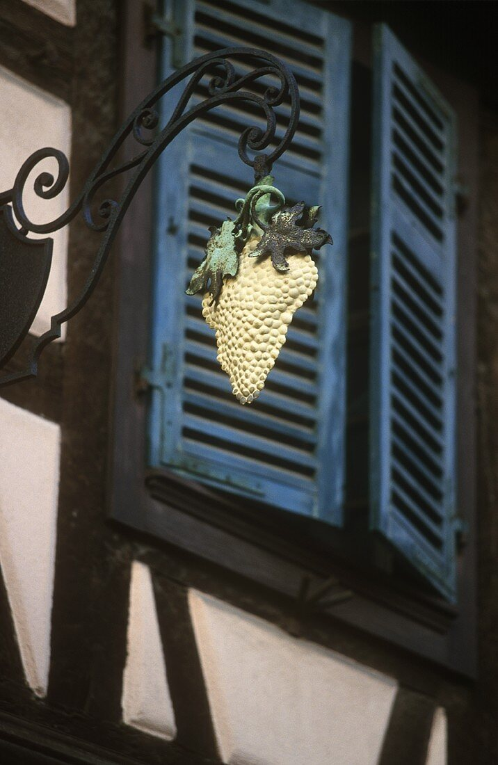 Grape sign on a house in Riquewihr (Alsace)