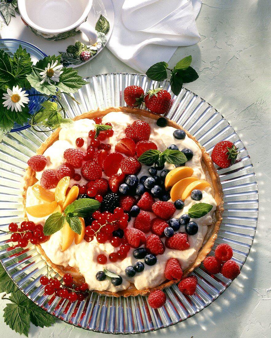 Colourful fruit gateau with orange cream on cake plate