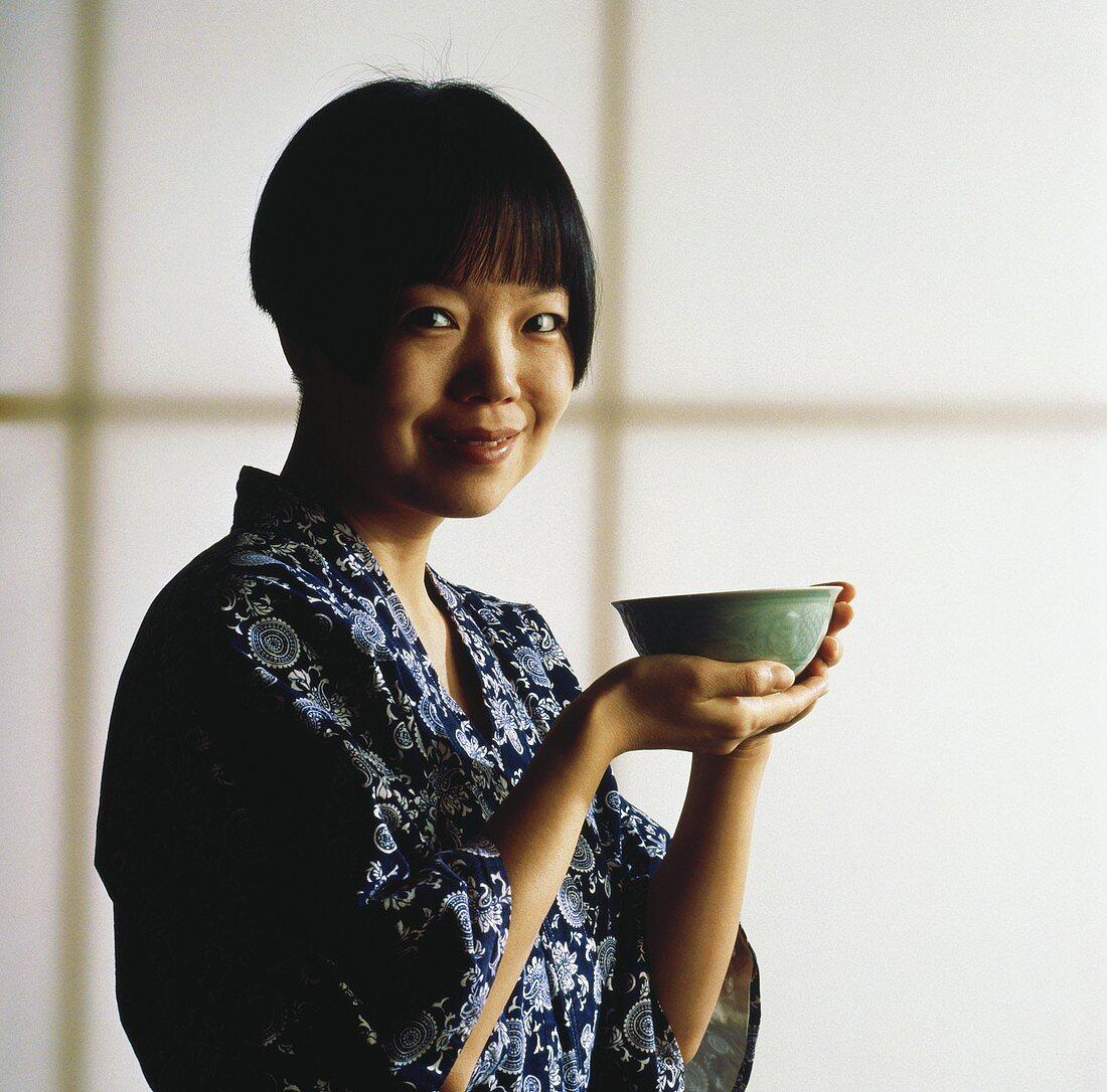 Asian woman holding bowl of tea