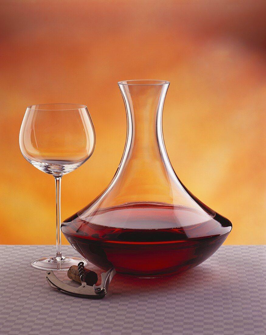 Carafe, empty red wine glass & corkscrew beside it