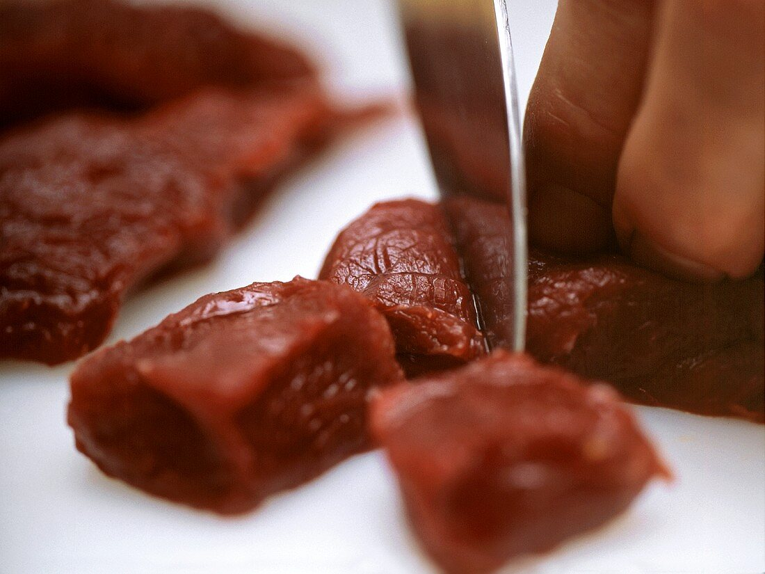 Cutting kangaroo meat into cubes