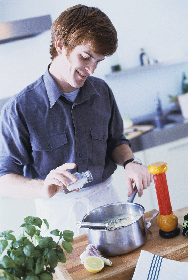 Young man seasoning soup with salt during cooking