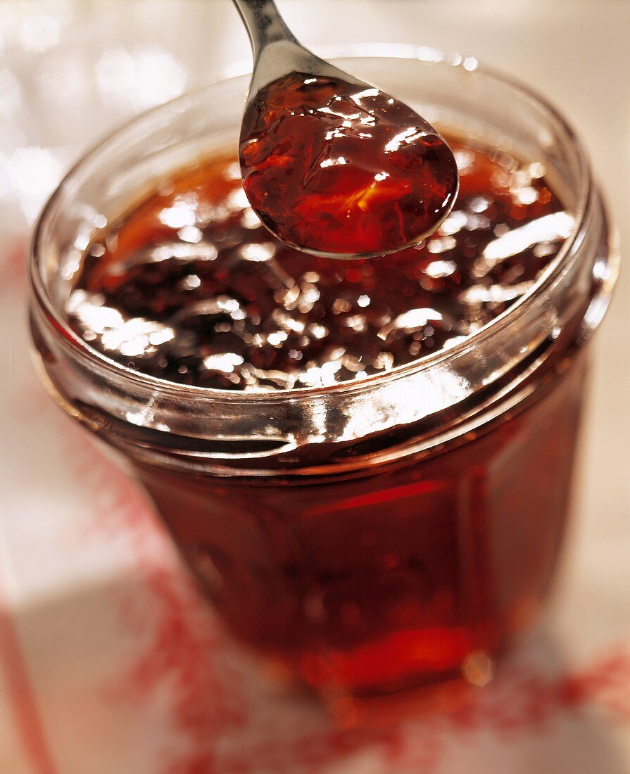 Blackcurrant jam in jar and on spoon