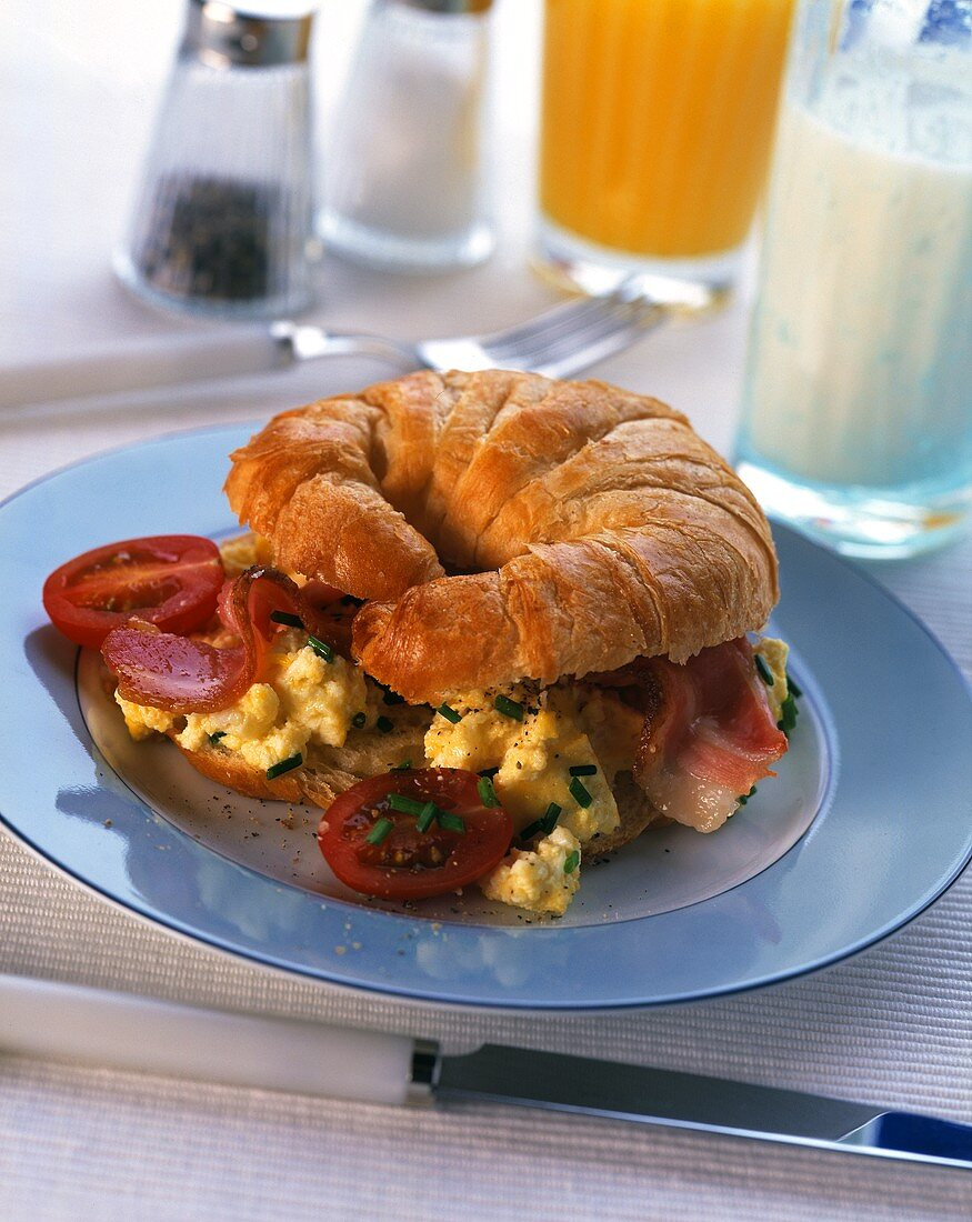 Croissant topped with scrambled egg, bacon & tomato