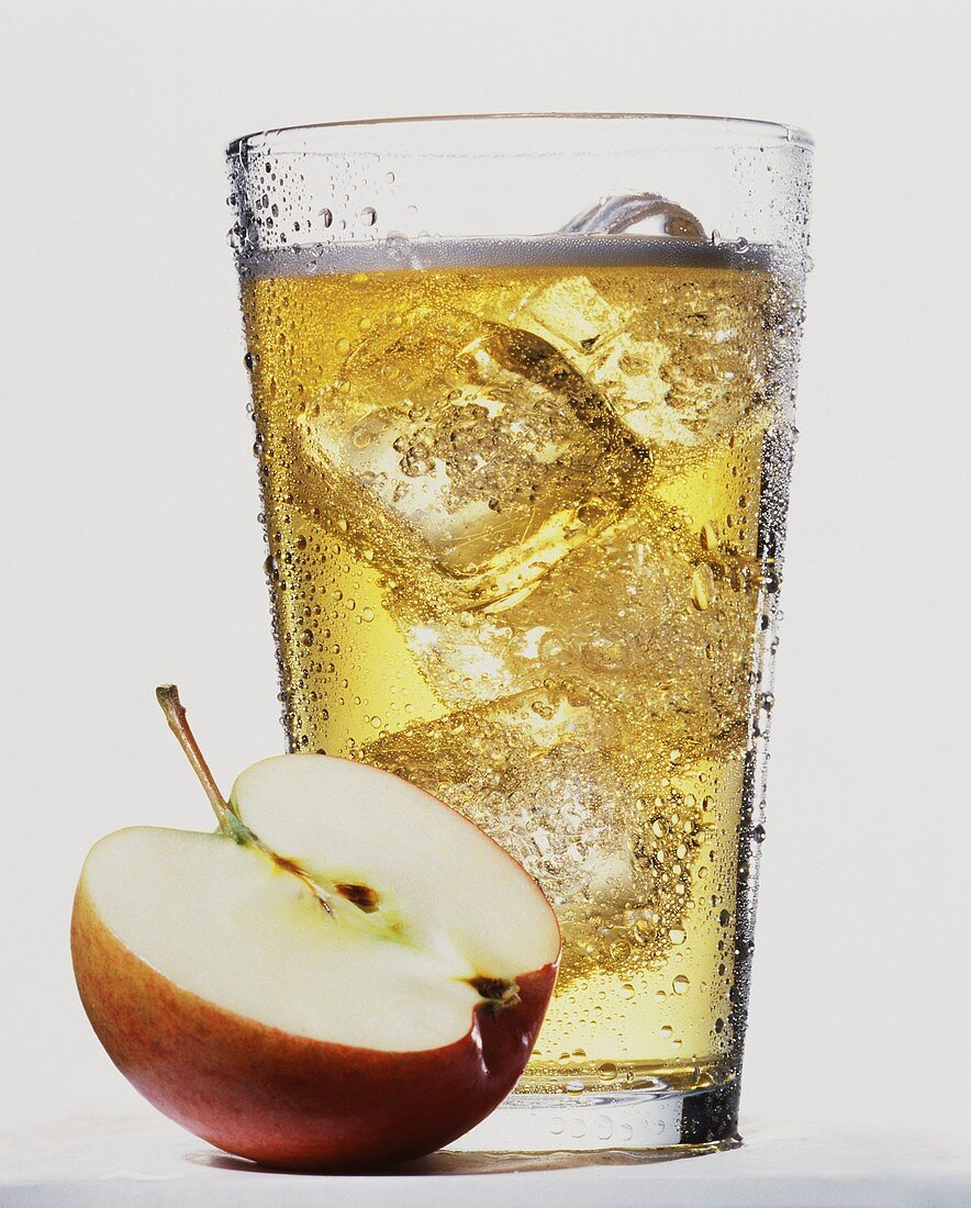 Apple juice drink with ice cubes, half an apple in front