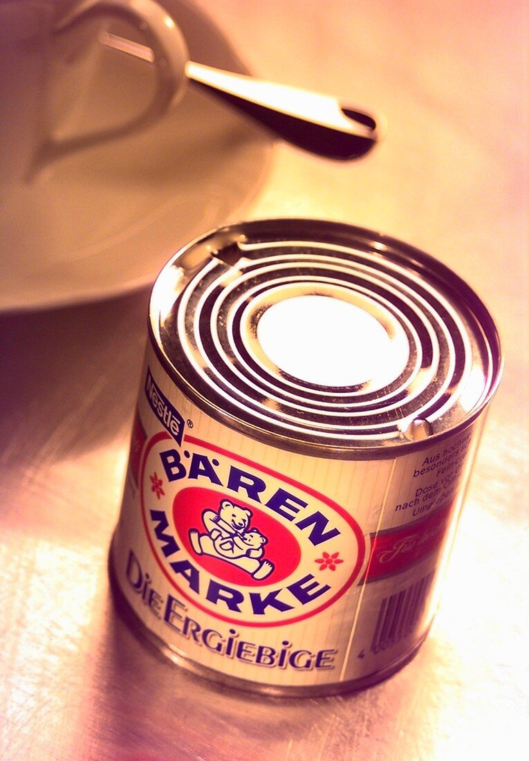 A tin of Bärenmarke coffee cream in front of a coffee cup