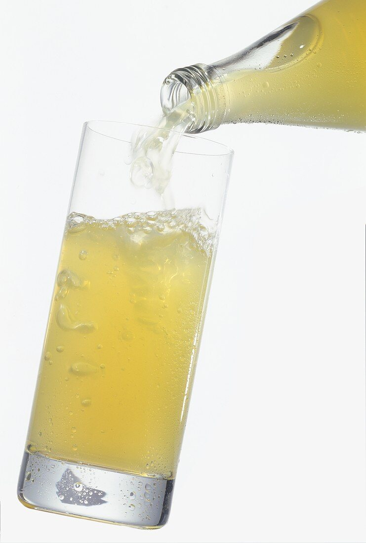 Pouring naturally cloudy apple juice drink into a glass