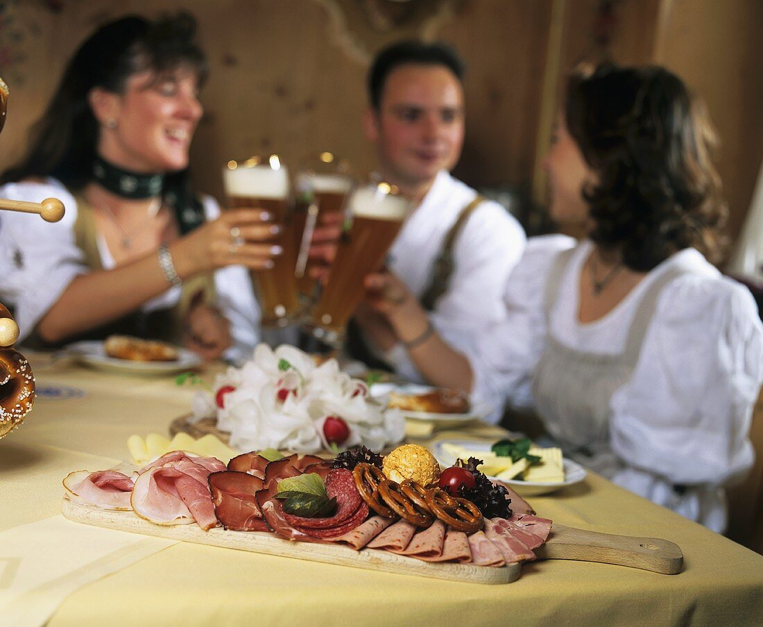 Young people with beer and hearty snack in inn (Andechs)