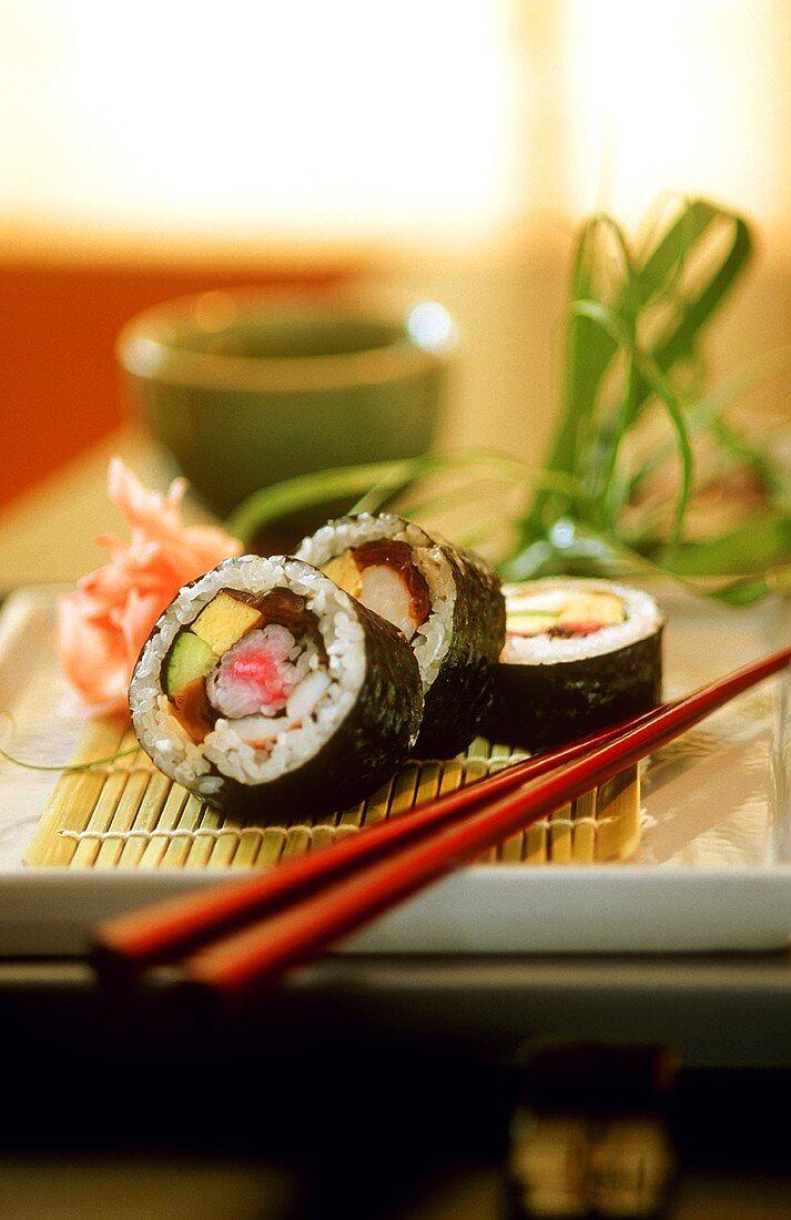 Several futo-maki on bamboo mat, chopsticks beside it