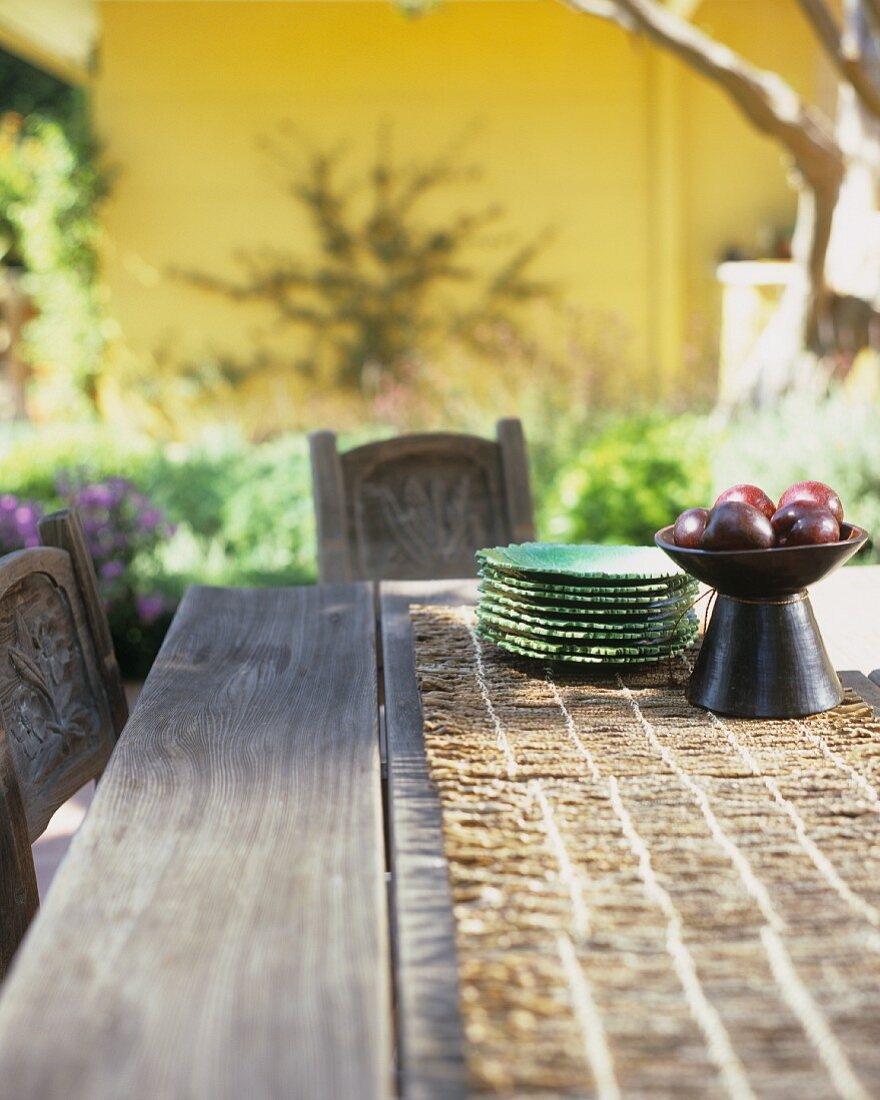 Wooden table in open air with a bowl of plums & pile of plates