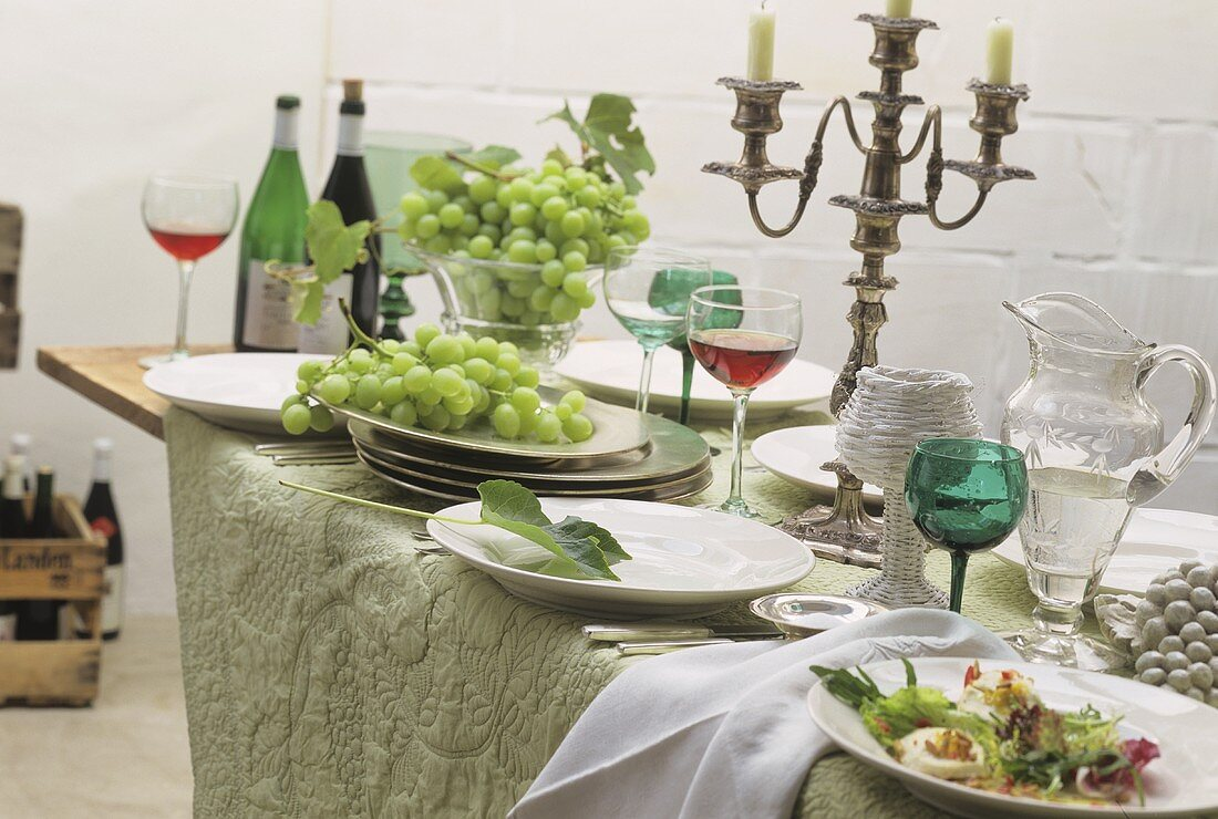 Improvised buffet on folding table with wine, grapes, salad