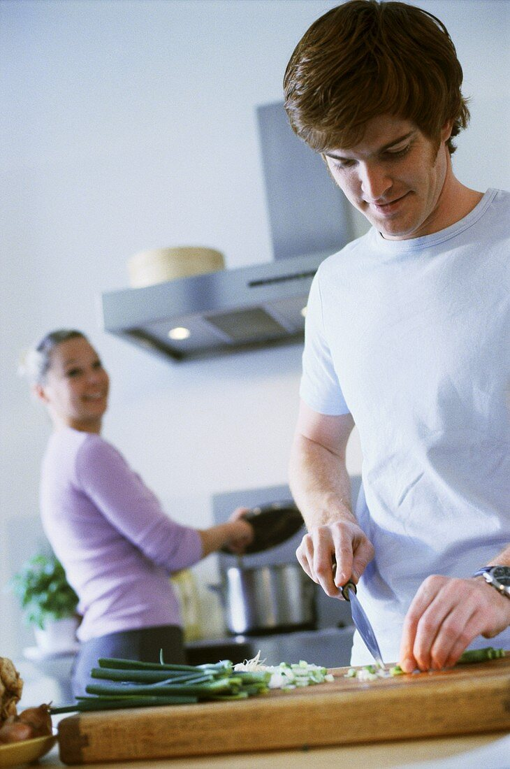 Young man cutting onion in kitchen